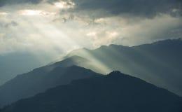 Landskap - solstrålar till och med molnet över kullar Arkivfoto