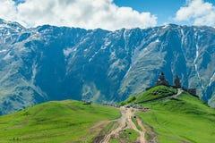 Landskap som förbiser gränsmärket Gergeti - Treenighetkyrka på bakgrunden av de pittoreska bergen med snöig maxima, royaltyfria bilder