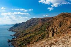 Landskap sommar, dag, Krim, berg, hav, udde Megan, sikt uppifrån av kustlinjen och horisonten royaltyfria bilder