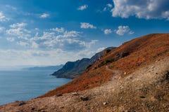 Landskap sommar, dag, Krim, berg, hav, udde Megan, sikt uppifrån av kustlinjen och horisonten arkivbild