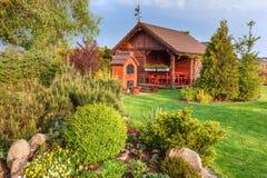 Landskap sommarträdgård med grillfesten och träsummerhousegräsplanträd, blomsterrabatter, Arkivfoto