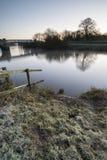 Landskap vintersurnise av floden och frostiga fält Arkivbilder