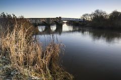 Landskap vintersurnise av floden och frostiga fält Arkivfoton