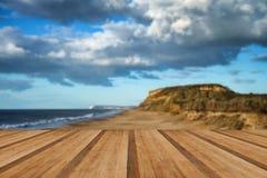 Landskap vivdsolnedgången över stranden och klippor med träplankor f Fotografering för Bildbyråer