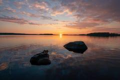 Landskapbild av en solnedgång bak lugna spegelcl Arkivbild