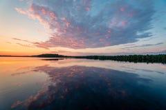 Landskapbild av en solnedgång bak lugna spegelcl Royaltyfri Foto