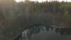 Landskape de forêt avec un lac Les gens près de l'eau waching une belle vue Tir du bourdon banque de vidéos