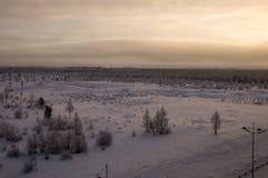 Landskape del invierno con el bosque en nieve en la puesta del sol de la tarde north Foto de archivo
