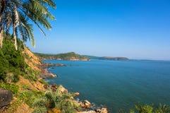 Landskapet är den härliga steniga kusten med palmträdet, det blåa havet och molnfri himmel i Om-stranden, Karnataka, Indien Arkivbilder