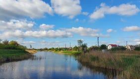 Landskapet av bygden flod himmel, moln, hus Arkivbild