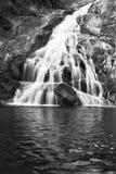 Landskapet av den lilla vattenfallet som applåderar över, vaggar med en lång exponering royaltyfri foto