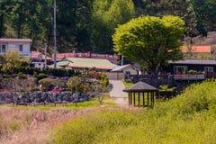 Landskapet av ett litet parkerar med en trägazebo Arkivfoton