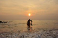 Landskapet av havet, som har fiskaren, fiskade med netto och molnig himmel i morgon Royaltyfri Fotografi