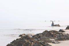 Landskapet av stranden och havet, som har fiskaren, fiskade med netto och molnig himmel i morgon Fotografering för Bildbyråer