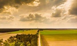 Landskapet i den norr tyska heden nära Celle, med ett litet stycke av skogen, ängar, fält och en TV står högt på horisonten, dram royaltyfria foton