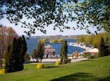 Landskapet i vår i staden parkerar att förbise sjön Arkivbild
