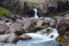 Landskapet med den lilla vattenfallet, floden med klart vatten och vaggar, Island Royaltyfria Foton