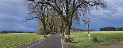 Landskapet med krucifix, träd-linjen och ängar stormar kort förr Arkivfoton
