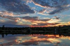 Landskapet solnedgång över sjömolnen reflekteras i vattnet arkivfoto