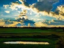 Landskapfoto av solljus som sprider till och med molnen ovanför ett damm royaltyfria bilder