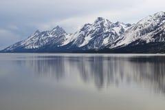 Landskapfotoet av snö täckte berget med sjön i förgrund arkivbilder