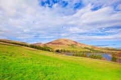 Landskaplandskap av grön dal, kulle, flod och molniga blått s Royaltyfri Fotografi