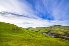 Landskaplandskap av grön dal, kulle, flod och molniga blått s Arkivfoton