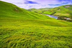 Landskaplandskap av grön dal, kulle, flod och molniga blått s Fotografering för Bildbyråer