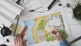 Landskapsarkitekt som arbetar på ett trädgårds- designplan stock video