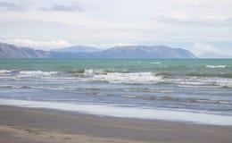 Landskapsikt av försiktiga vågor som rullar in på den Raumati stranden, Nya Zeeland arkivbild