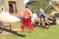 Landsknechts with visitor shooting from cannon Stock Photo