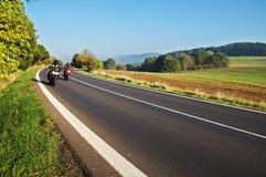 Landslandskap med en asfaltväg Två motorcyklar på vägen Fotografering för Bildbyråer