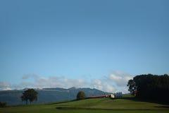 Landslandskap med grön gräsmatta royaltyfria bilder