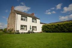 Landslantgårdhus med gräsmatta Royaltyfri Fotografi