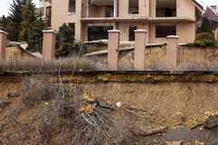 Landslide caused by rains of hurricane destroyed expensive cottages and houses. Destroyed house, cottage, large cracks, chips,. Slabs. Broken asphalt shifted royalty free stock image