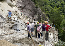 Landslide:dangerous move. A large landslide in China.Some people are carefully moving across the landslide and several workers are  working for repairing the Stock Images