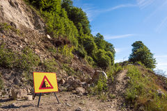 Landslide in forest dirt road and warning sign. Stock Image