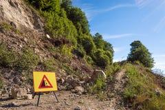 Landslide in forest dirt road and warning sign. Landslide stopping a forest dirt road and warning sign stock image