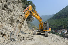 Landslide hazard at Rudraprayag of Garhwal Himalaya. Bulldozer cleaning landslide from road in Rudraprayag.The Landslide hazard evaluation factor(LHEF) rating Stock Photo