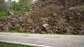 Landslide on the mountain road..Camiguin island Philippines. Landslides and rockfalls on the road in the mountains. Mud and rocks blocking the road.Destroyed Stock Photography