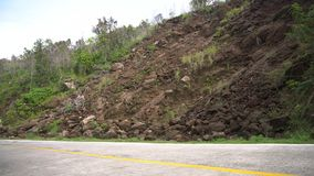 Landslide on the mountain road..Camiguin island Philippines. Landslides and rockfalls on the road in the mountains. Mud and rocks blocking the road.Destroyed Royalty Free Stock Image