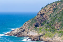 Landspitze, die in das Meer mit Eisenbahntunnel und Bahnen hervorsteht Lizenzfreie Stockfotografie