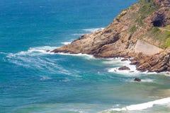 Landspitze, die in das Meer mit Eisenbahntunnel und in die Bahnen nahe bei Bucht hervorsteht Stockfotos