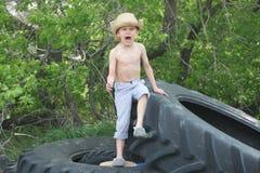 Landspojke på stora gummihjul Arkivbild
