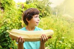 Landspreteenpojke med stort le för squash som är lyckligt på slut för sommarträdgårdbakgrund upp ståenden arkivfoto