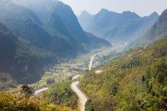 Landssikt med kurvvägen, det gula trädet och berget i det Ha Giang landskapet, Vietnam Royaltyfria Foton