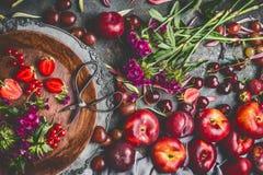 Landsstilleben med frukter och bär för olik sommar säsongsbetonade med trädgårds- blommor i platta på mörk lantlig bakgrund royaltyfri foto