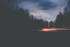 Landstraße in der Dunkelheit mit Autolicht schleppt und Windgenerator lizenzfreie stockfotos