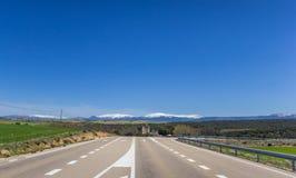 Landstraße, die zu eine Strecke des schneebedeckten Bergs führt Lizenzfreies Stockbild