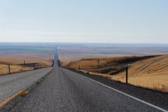 Landstraße durch das Rollen des goldenen Ackerlands Lizenzfreie Stockfotografie